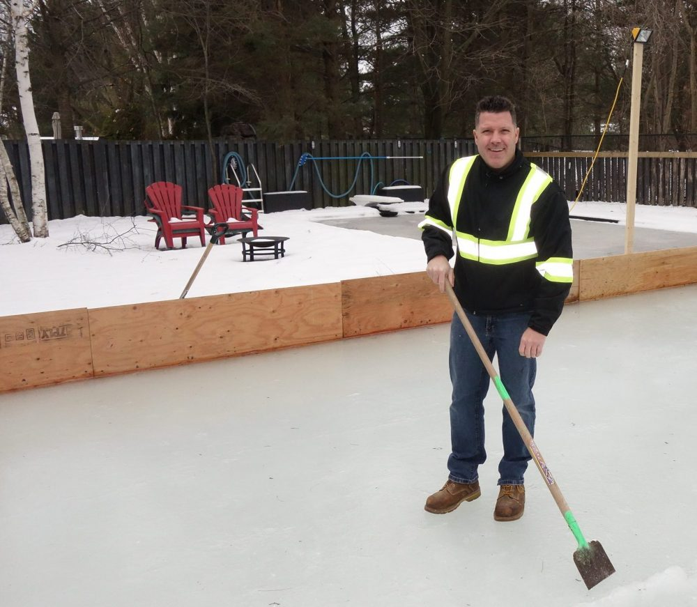 Keith Travers cleans the ice on the homemade rink