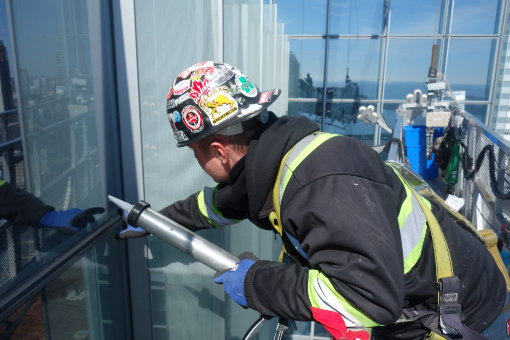 glazier caulks windows in skyscraper Toronto
