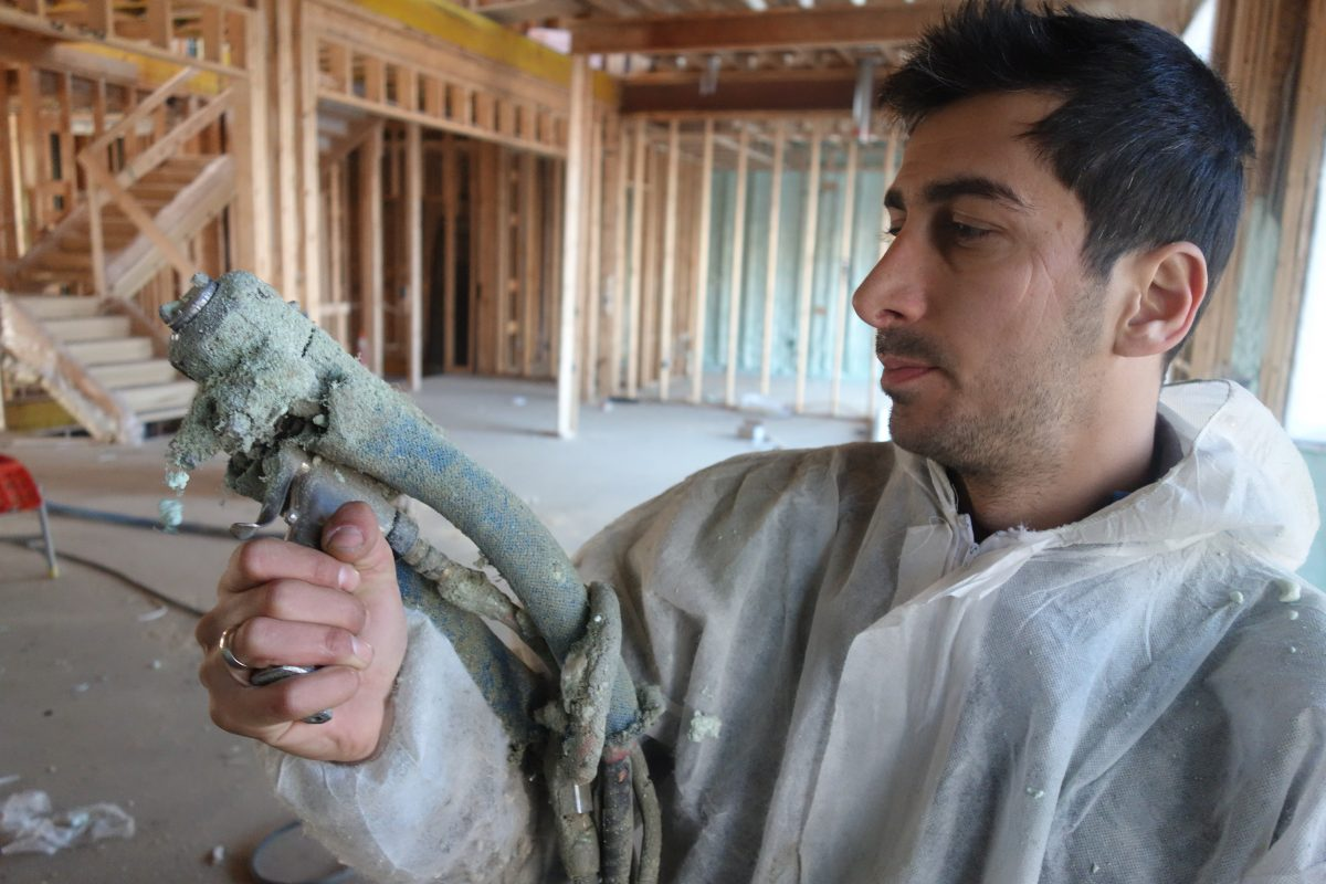 George Shimi holds spray foam gun inside new Toronto home insulation