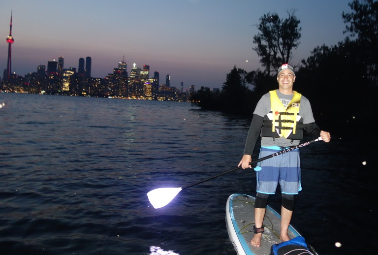 Niv is paddlebaording at night in Toronto